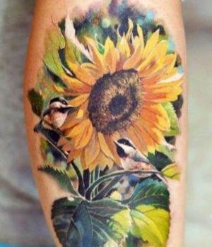 tatuaje realista de girasoles y pajaros