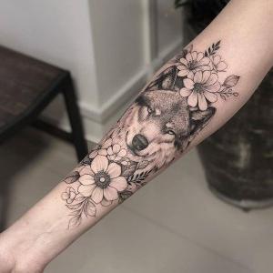 tatuaje en el brazo de lobo con flores