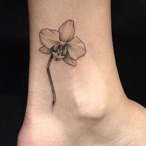 tatuaje chido de oequídea en el tobillo