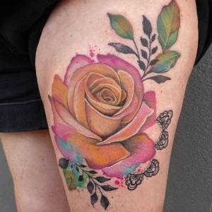 tatuaje para mujer de rosa en el muslo